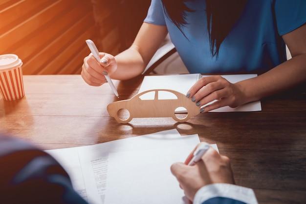 Mann unterschreibt eine autoversicherung, der agent hält das holzautomodell.