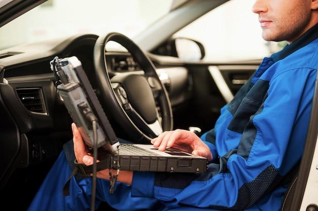 Mann untersucht auto. selbstbewusster junger mann, der an einem speziellen laptop arbeitet, während er in einem auto in der werkstatt sitzt