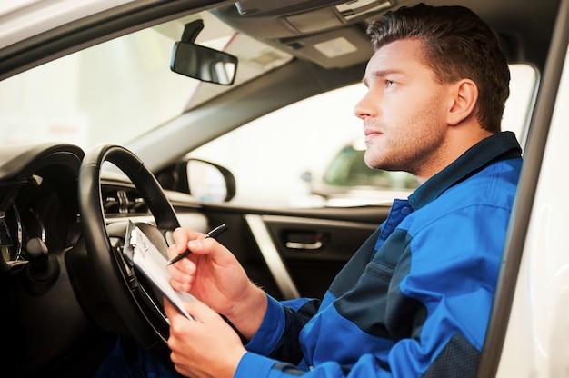 Mann untersucht auto. selbstbewusster junger mann, der auto untersucht und etwas in die zwischenablage schreibt, während er in einem auto in der werkstatt sitzt sitting