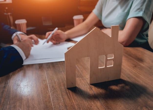 Mann unterzeichnen eine hausversicherung auf wohnungsbaudarlehen. immobilienmakler mit kunden vor vertragsunterzeichnung.