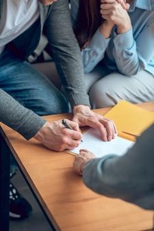 Mann unterzeichnet dokument vor frau und makler