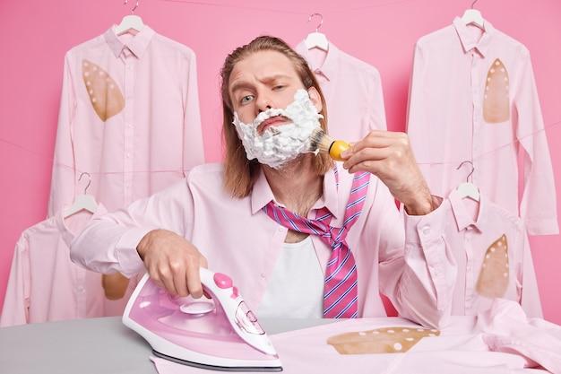 Mann verbrannte kleidung beim bügeln und rasieren, der mit der hausarbeit beschäftigt ist, erledigt verschiedene aufgaben gleichzeitig und posiert auf hemden auf kleiderbügeln. haushälterin bügelt zu hause