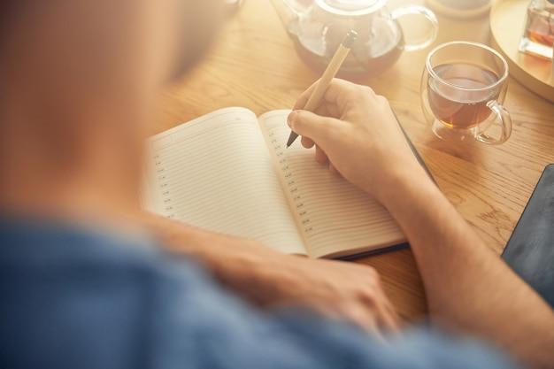 Mann verbringt zeit damit, wichtige informationen zu notieren und heißen schwarzen tee zu trinken
