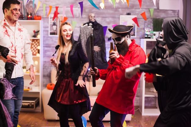 Mann verkleidet wie ein pirat, der eine axt hält, die bei halloween-feiern mit seinen freunden tanzt.