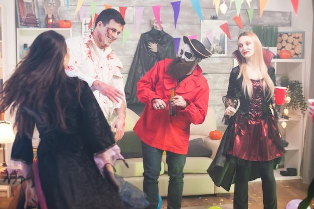 Mann verkleidet wie ein unheimlicher zombie mit blut im gesicht bei der halloween-feier mit seinen freunden.