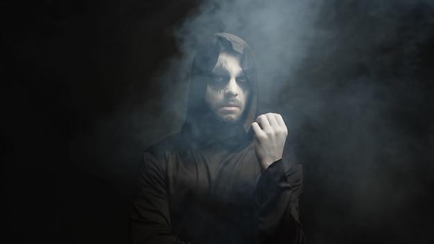 Mann verkleidet wie sensenmann für halloween-party auf schwarzem hintergrund mit rauch
