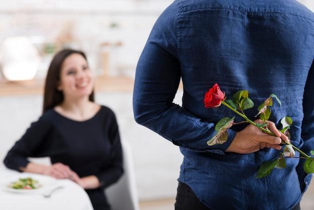 Mann versteckt eine rose vor seiner freundin