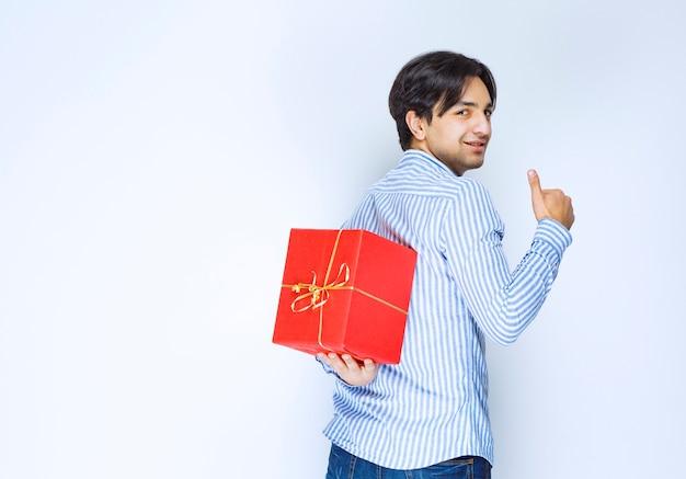 Mann versteckt eine rote geschenkbox hinter sich. foto in hoher qualität