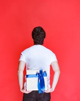 Mann versteckt eine weiße geschenkbox hinter sich, um eine überraschung zu machen.