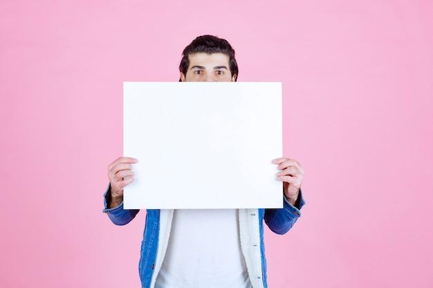Mann versteckt sein gesicht hinter einer quadratischen denktafel