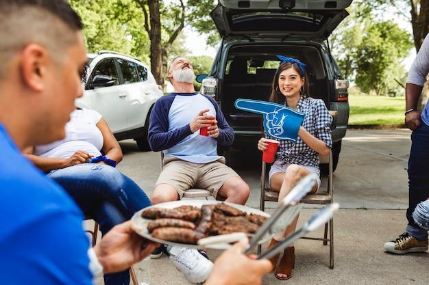 Mann verteilt burger auf einer heckklappenparty