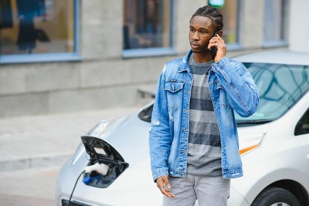 Mann verwenden smartphone während des wartens und stromversorgung verbinden sich mit elektrofahrzeugen zum laden der batterie im auto