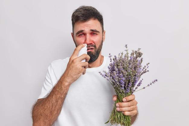 Mann verwendet aerosolspray für verstopfte nase hält lavendelstrauß hat allergie-krankheitssymptom trägt lässiges t-shirt isoliert auf weiß
