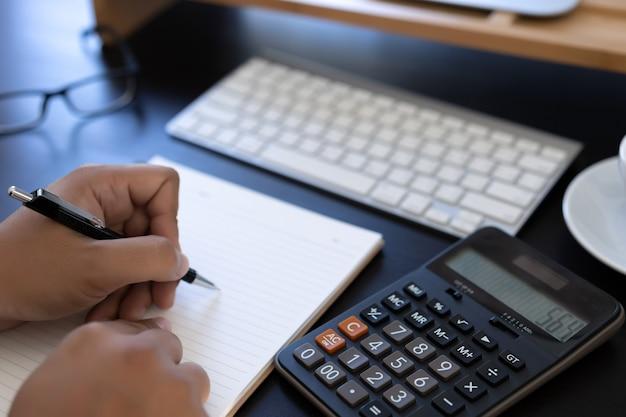 Mann verwendet rechner, um die kosten im büro zu berechnen