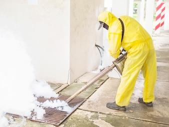 Mann verwendet thermische Nebelmaschine, um die Ausbreitung von Moskitos zu schützen