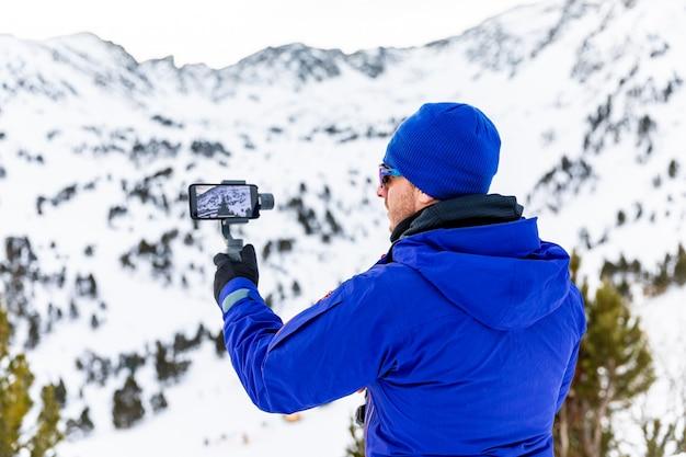 Mann video mit seinem telefon und stabilisator aufnehmen
