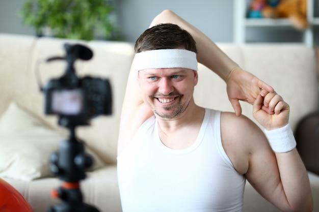 Mann vlogger, der übung für handporträt tut. glücklicher sportler, der eignungstraining auf digitalkamera für sport vlog notiert.