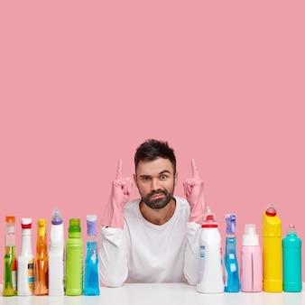 Mann vom reinigungsdienst, hat verwirrten gesichtsausdruck, zeigt mit beiden zeigefingern nach oben