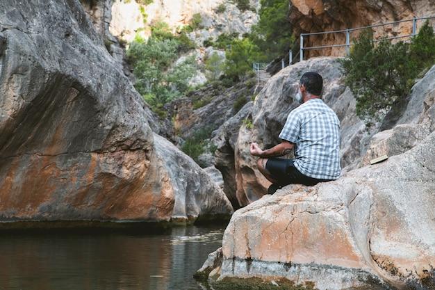 Mann von hinten meditiert auf einem felsen am fuße eines bergflusses