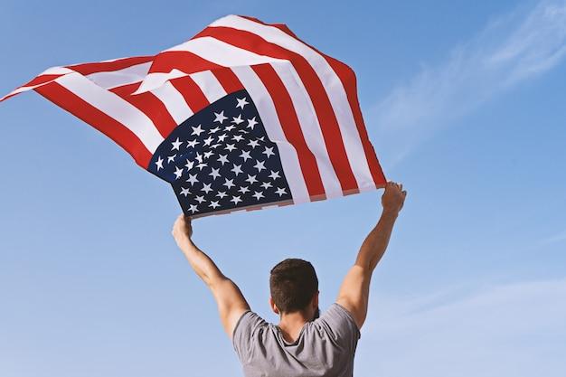 Mann von hinten mit den angehobenen händen und der wellenartig bewegenden amerikanischen flagge