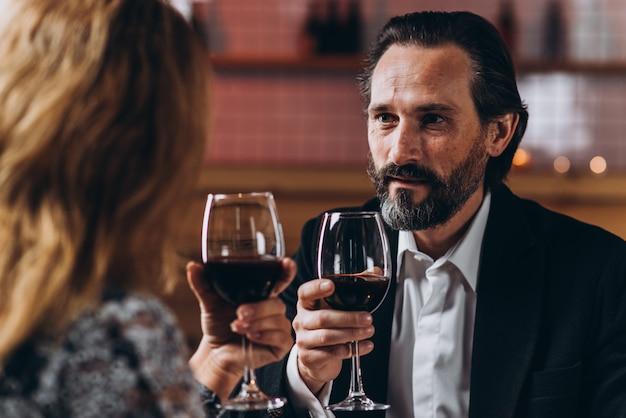 Mann von mittlerem alter betrachtet die frau und wirft mit ihr ein glas rotwein auf