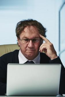 Mann von mittlerem alter im formalwear, das artikel auf geschäft an seinem laptop bei der arbeit liest