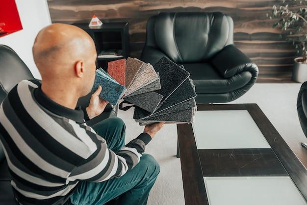 Mann wählt den boden oder teppich zu seiner neuen wohnung