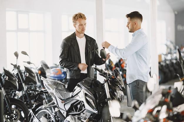 Mann wählte motorräder im motoladen. mann in einer schwarzen jacke. manager mit client.