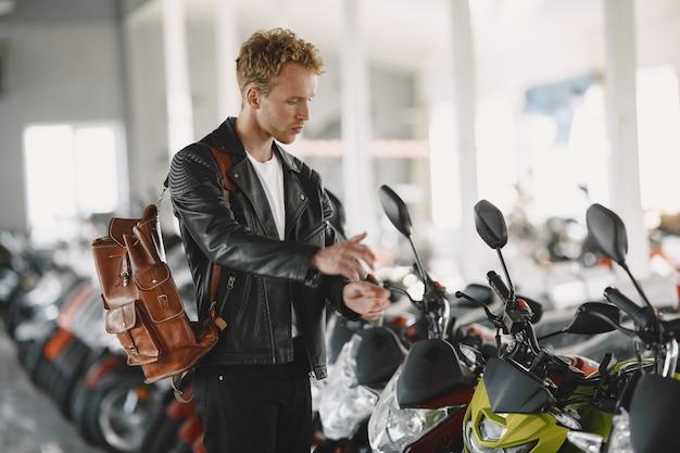 Mann wählte motorräder im motoladen. mann in einer schwarzen jacke.