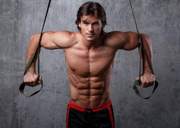 Mann während des trainings mit tragegurten