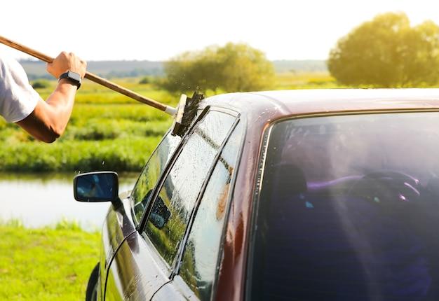 Mann wäscht altes auto. reinigung des fahrzeugs im freien. nasser mopp.
