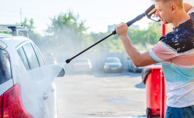 Mann wäscht auto mit hochdruckwasser