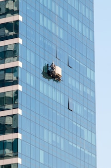 Mann wäscht fenster auf hochhaus
