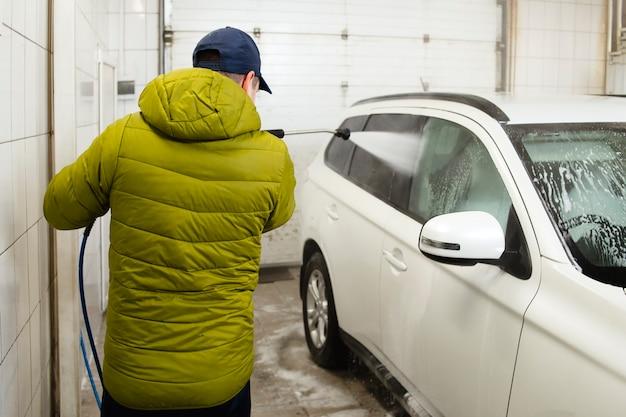 Mann wäscht sein auto mit hochdruckwäsche