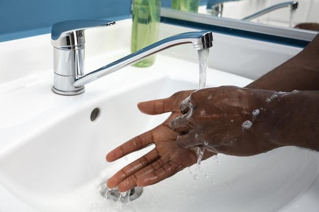Mann wäscht sich sorgfältig die hände mit seife und desinfektionsmittel, nahaufnahme. verhinderung der ausbreitung des lungenentzündungsvirus, schutz vor coronavirus-pandemie. hygiene, sanitär, sauberkeit, desinfektion. sicherheit.