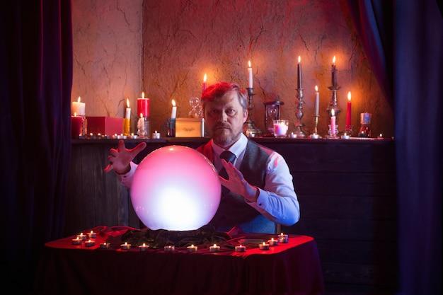Mann wahrsagerin mit beleuchteter kristallkugel