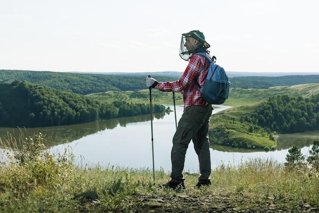 Mann wanderer mit netzen von moskitos beim wandern in der nähe des sees im freien.