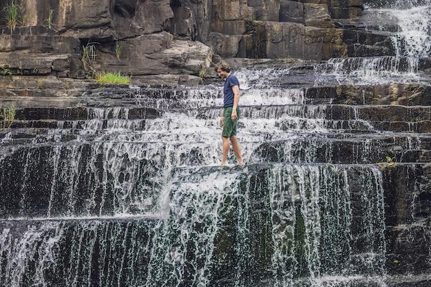 Mann wanderer, tourist auf der oberfläche des amazing pongour wasserfalls ist berühmt und am schönsten im herbst in vietnam