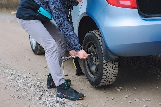 Mann wechselt reifen mit rad am auto
