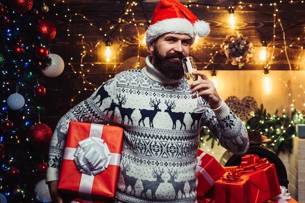 Mann weihnachtsmann. neujahrs-weihnachtskonzept. stylingmann mit einem langen bart, der auf dem hölzernen hintergrund aufwirft. weihnachtsmann zu hause