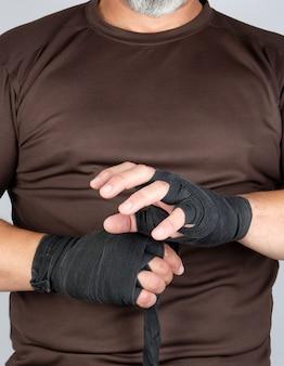 Mann wickelt seine hände im schwarzen textilverband für sport ein