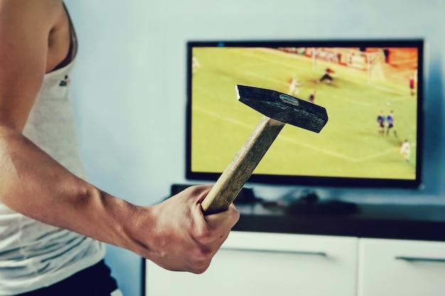 Mann will den fernseher kaputt machen. der typ schlug mit einem hammer auf den bildschirm.