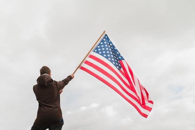 Mann winkt amerikanische flagge