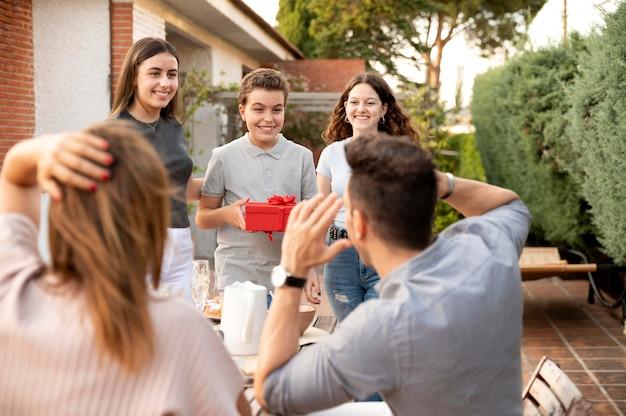 Mann wird beim familientreffen mit geschenk überrascht