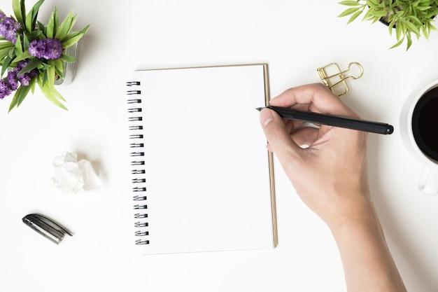 Mann wird etwas auf leere notizbuchseite schreiben. draufsicht, flach zu legen.