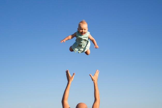 Mann wirft baby gegen den blauen himmel
