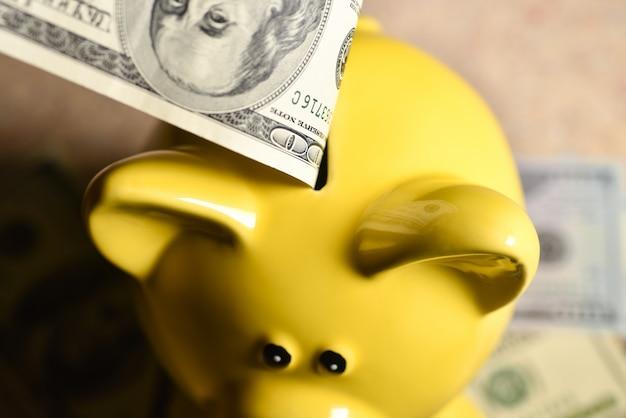 Mann wirft eine rechnung in ein gelbes sparschwein.