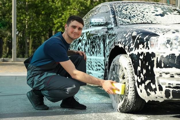 Mann wischt das auto mit einem schwamm ab. autowäsche. klares autokonzept