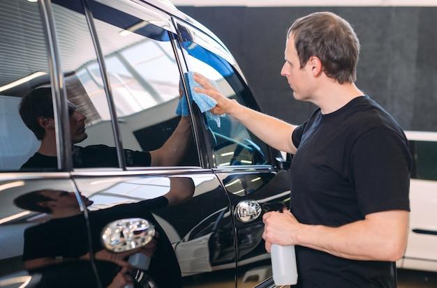 Mann wischt mit einem stoffkörper eines brillanten autos.