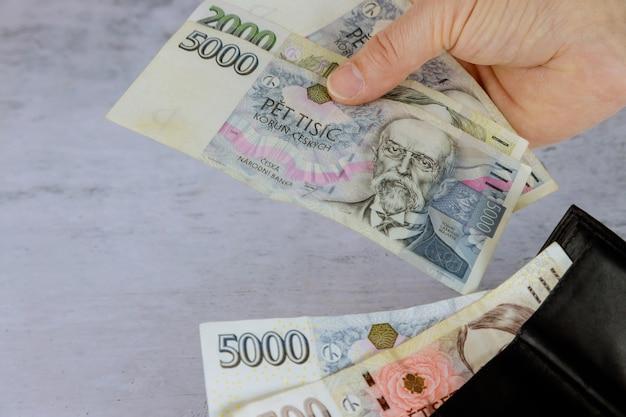 Mann zählt tschechische korun in seiner brieftasche